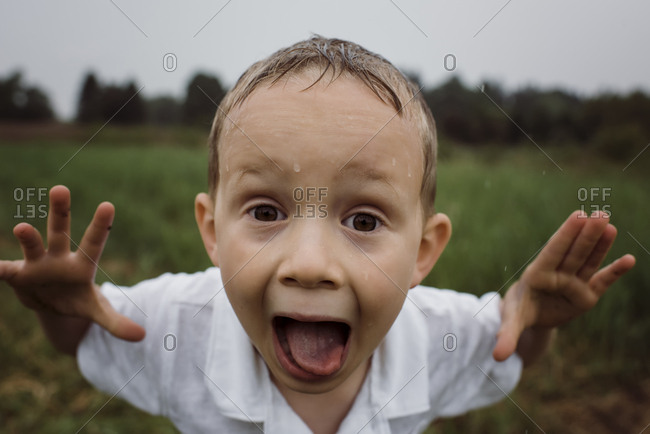 Portrait of wet boy screaming while standing against sky at park during rainy season