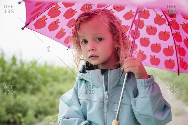 Portrait of cute girl carrying pink umbrella while standing against plants during rainy season