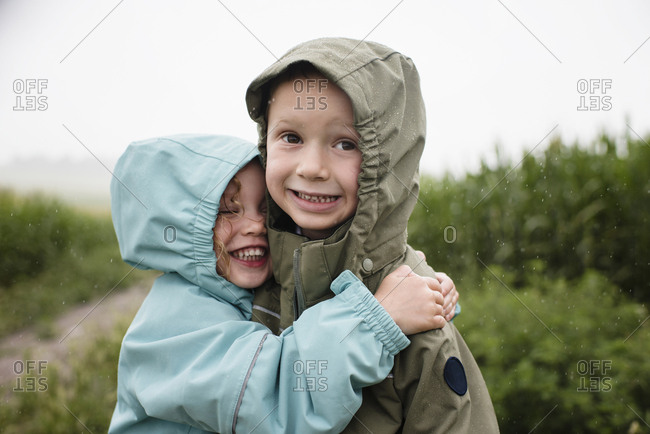 Happy sister embracing brother while standing against plants during rainy season