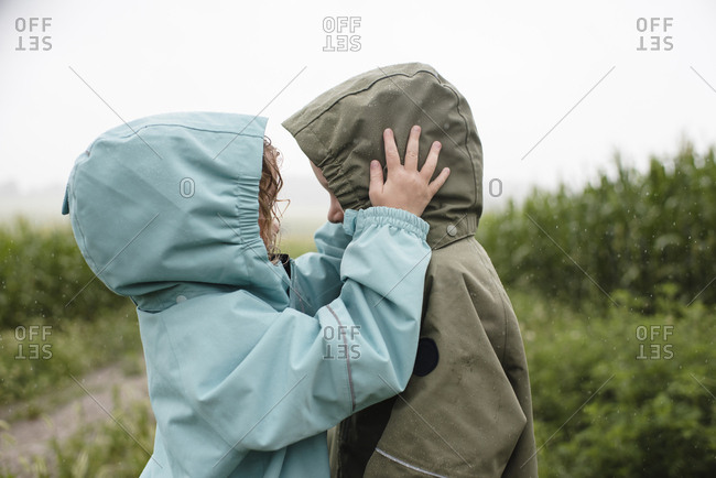 Side view of siblings in raincoats looking at each other while standing against plants during rainy season