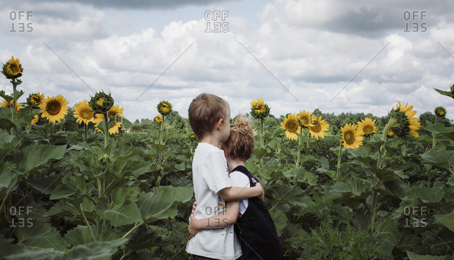 Side view of siblings embracing while standing amidst plants against cloudy sky