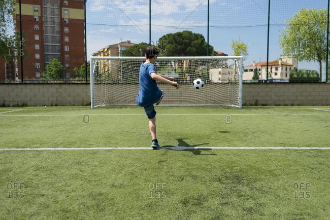 Rear view of boy kicking soccer ball towards net on field