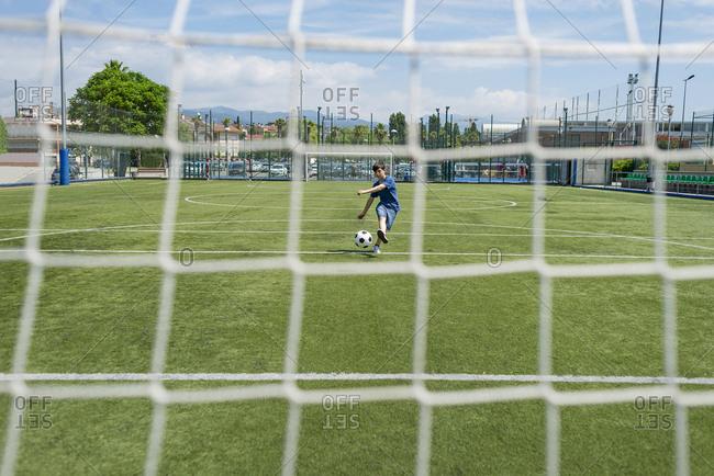 Boy kicking soccer ball against sky seen through net