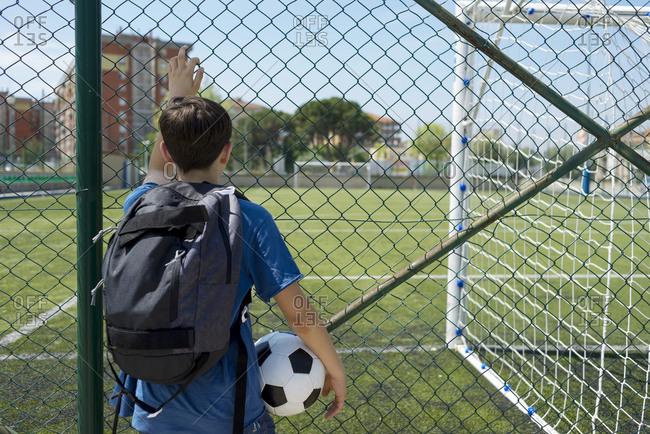 Rear view of boy with backpack holding soccer ball while standing by fence at dugout