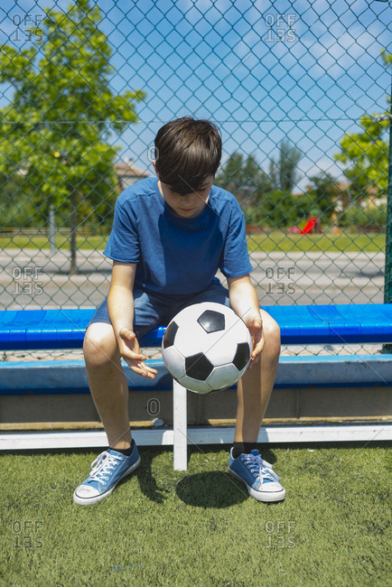 Boy holding soccer ball while sitting on bench by fence at dugout