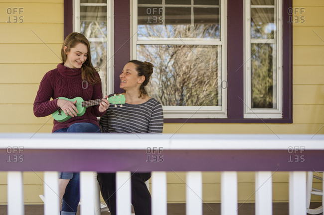 Happy mother looking at daughter playing guitar while sitting in balcony