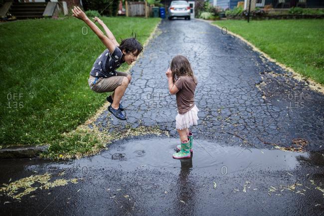 Side view of playful siblings enjoying on wet road during rainy season