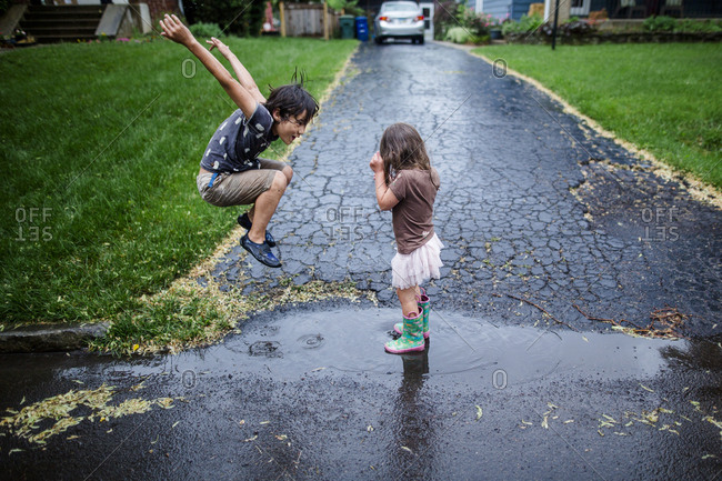 Side view of playful siblings enjoying on wet road during rainy season