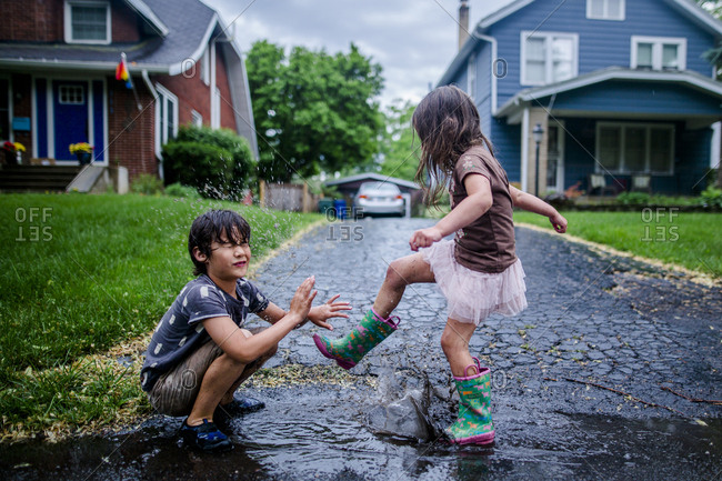 Side view of playful sister splashing puddle on brother during rainy season