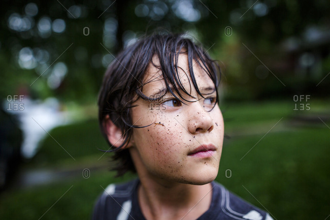 Close-up of thoughtful boy with dirty face standing at yard during rainy season