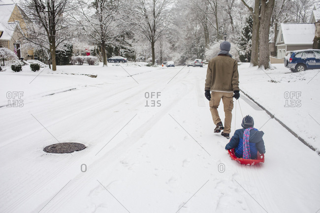 Rear view of father sledding daughter on snow covered road