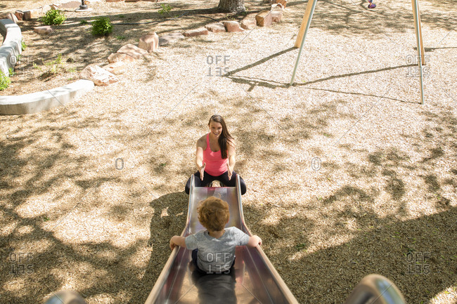 High angle view of son sliding towards mother on slide at playground