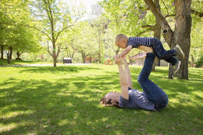 Side view of playful mother balancing son on legs at park