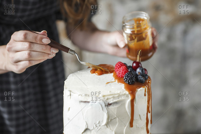 Midsection of woman icing cake with caramel and berry fruits at home