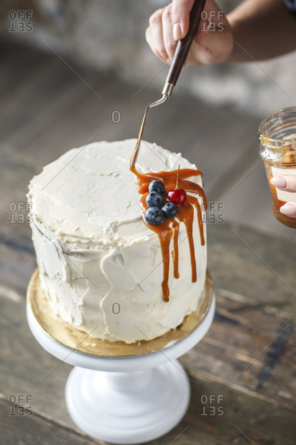 Cropped hands of woman icing cake with caramel and berry fruits on wooden table at home