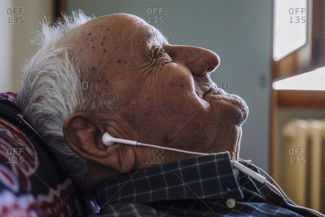 Close-up of thoughtful senior man listening music while relaxing on sofa at home