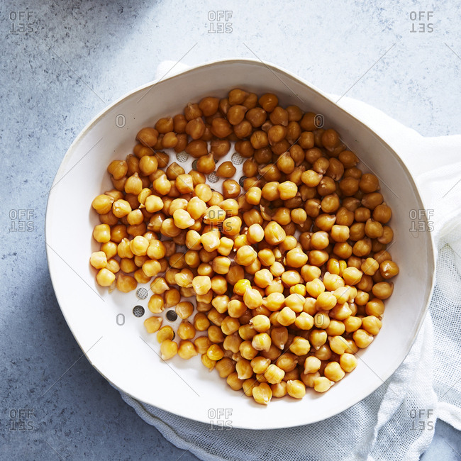 Overhead view of chick-peas in bowl with napkin on table