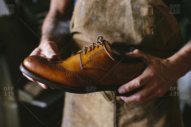 Midsection of craftsperson holding leather shoe while standing in workshop