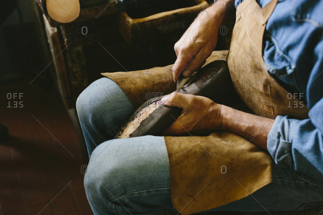 High angle midsection of craftsperson making shoe while sitting in workshop
