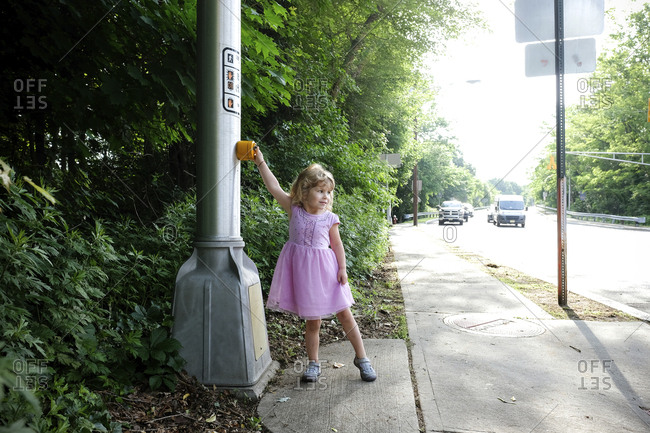 Cute girl looking away while pushing crosswalk button on road