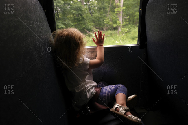 Side view of girl looking through window while traveling in bus