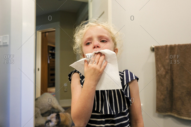 Close-up of girl crying with toothache while standing against wall at home