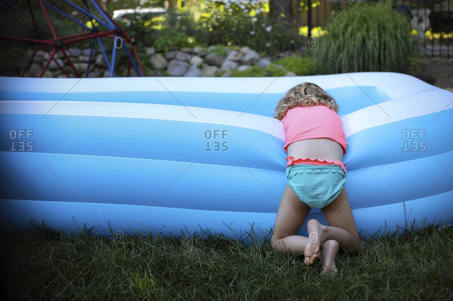 Rear view of girl leaning on blue wading pool at backyard
