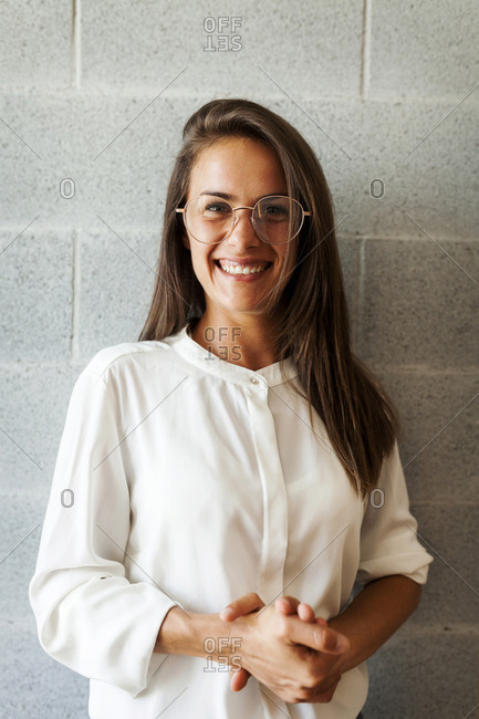 Portrait of happy woman wearing eyeglasses while standing against wall at home