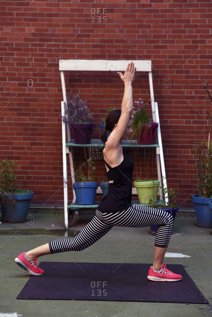 Side view of woman with arms raised practicing warrior 1 pose against brick wall