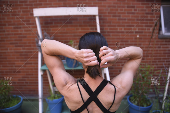 Rear view of woman tying hair while standing against brick wall