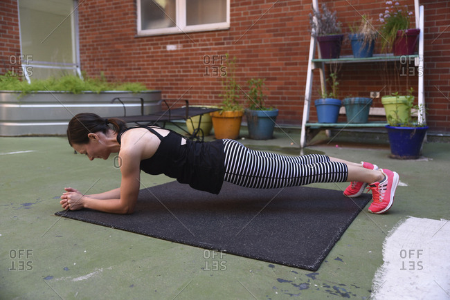 Side view of woman practicing plank position against brick wall