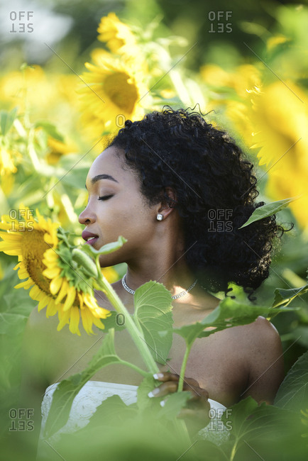 Close-up of bride with eyes closed standing amidst sunflowers at farm