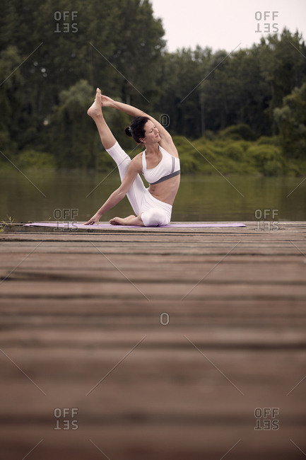 Woman practicing yoga on pier by lake against trees during sunset