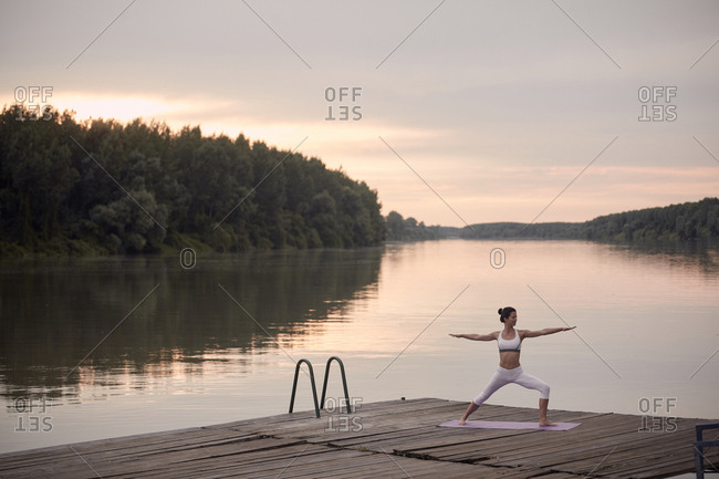 Woman practicing warrior 2 pose on pier by lake against cloudy sky during sunset