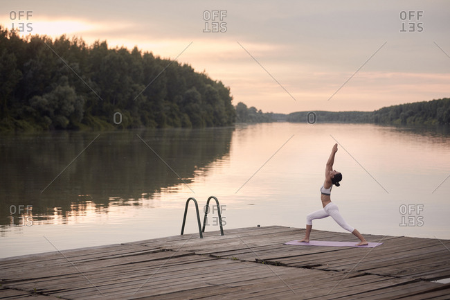 Woman practicing warrior 1 pose on pier by lake against cloudy sky during sunset