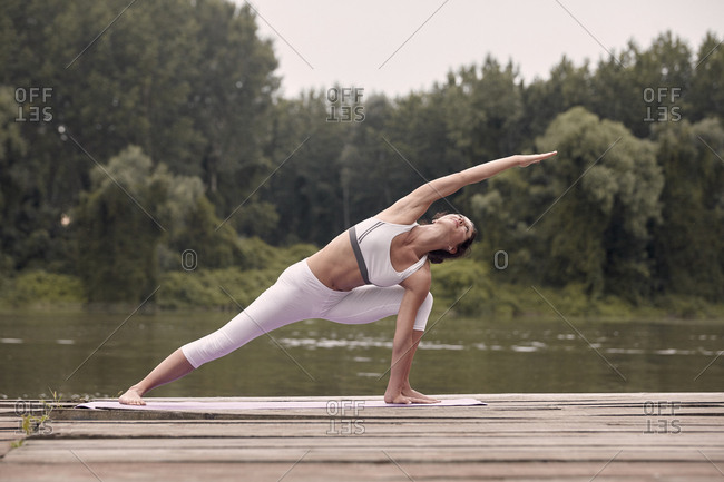 Woman practicing extended side angle pose on pier by lake against trees during sunset
