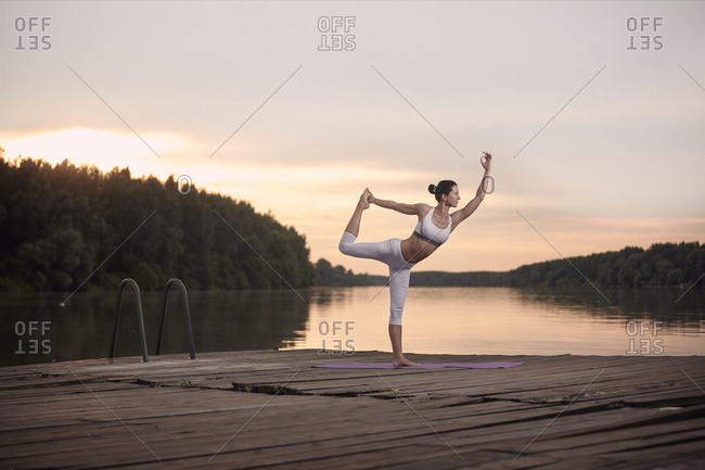 Woman practicing dance pose on pier by lake against cloudy sky during sunset