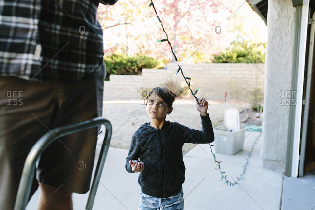Son looking at father hanging colorful string lights on house during Christmas