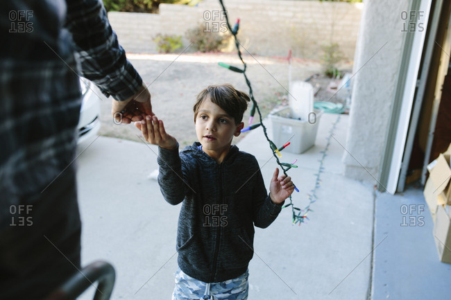 Son assisting father in hanging colorful string lights on house during Christmas