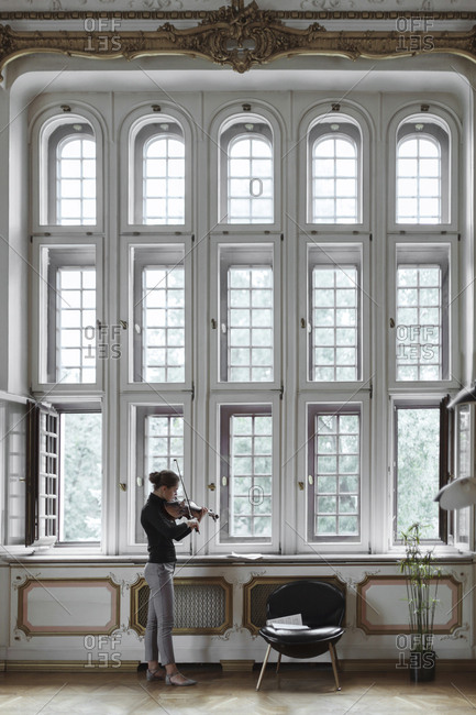 Side view of woman playing violin while standing by windows in mansion