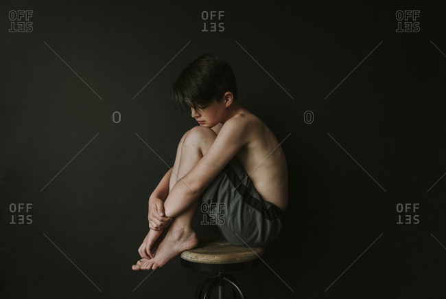 Side view of sad shirtless boy sitting on stool against black background