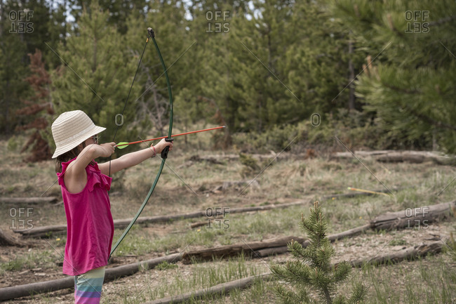 Side view of girl aiming with bow and arrow while standing against trees in forest