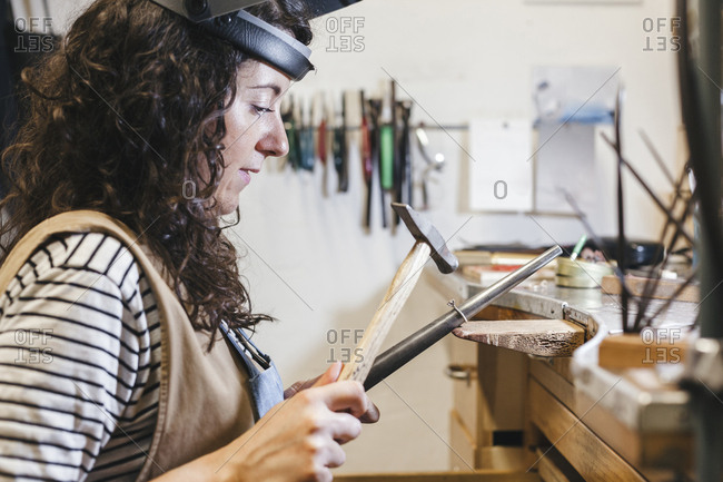 Side view of female craftsperson using hammer while shaping ring on table in workshop