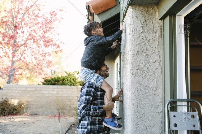Side view of father carrying son on shoulders hanging string lights on wall during Christmas