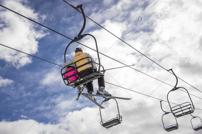 Rear view of father with daughter sitting on ski lift against cloudy sky during winter