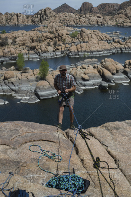 High angle view of man with climbing ropes standing on rock formation over lake during sunny day