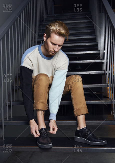 Full length of young man tying shoelace while sitting on steps at home