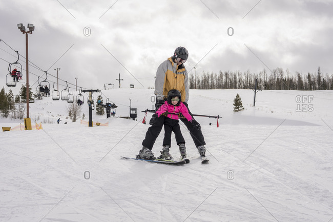 Father with daughter skiing on snow covered landscape against cloudy sky
