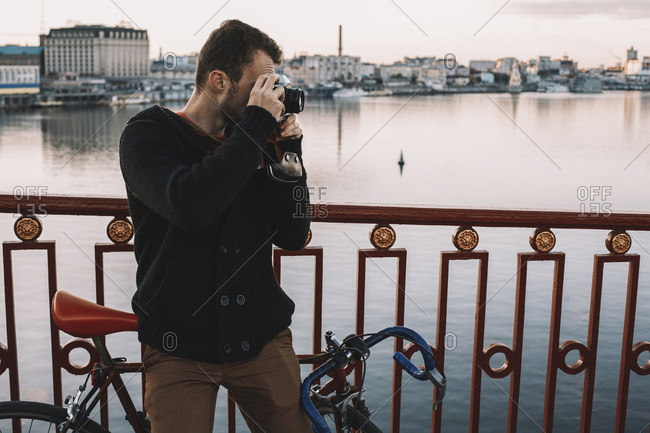 Cyclist photographing with camera while standing with bicycle on bridge over river in city during sunset