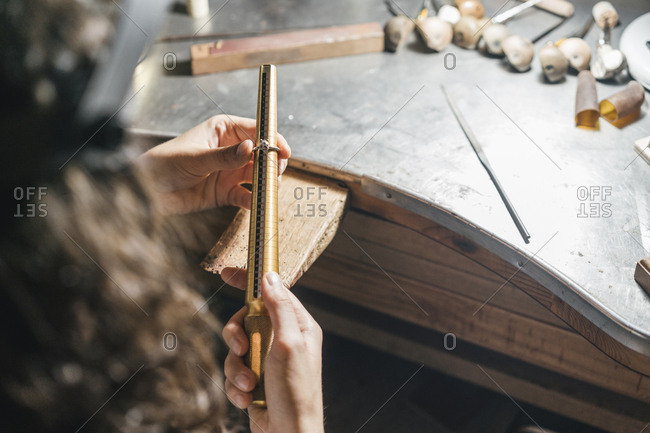 Cropped image of female student measuring ring over table in workshop